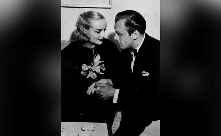 Carole Lombard and Russ Colombo hold hands as they stare into each other's eyes.