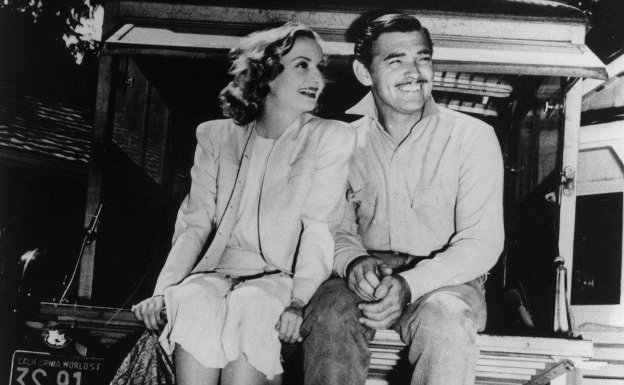 Carole Lombard and Clark Gable sit in the back of a vehicle on set.