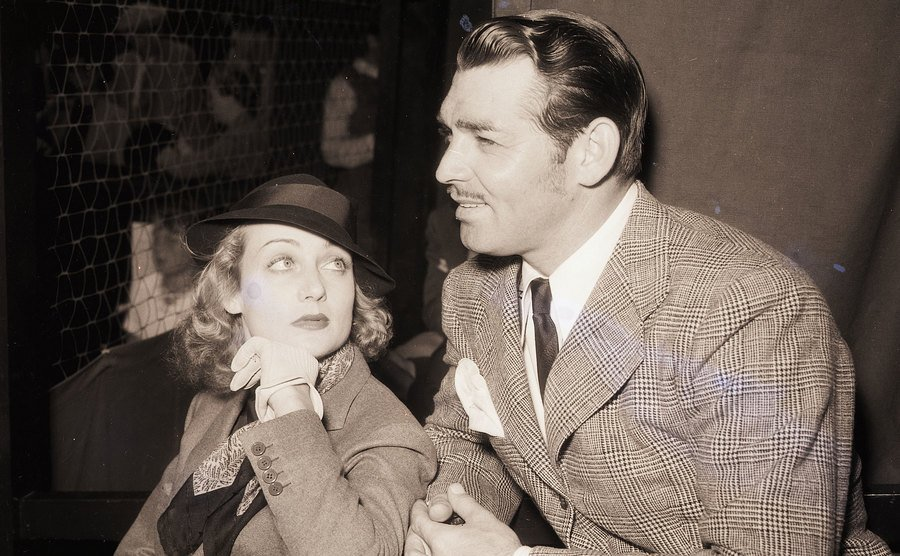 Clark Gable and Carole Lombard sit beside each other.