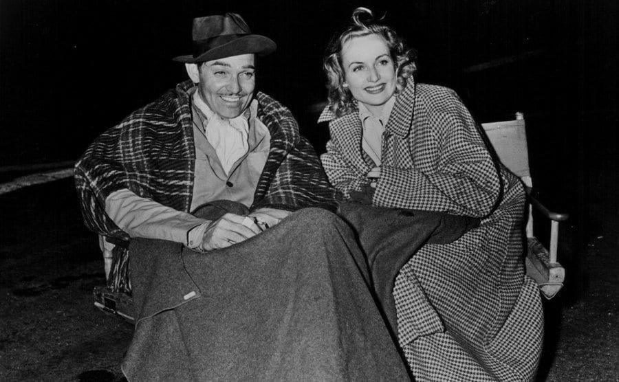 Clarke Gable and Carole Lombard, sitting together wearing heavy coats and blankets.