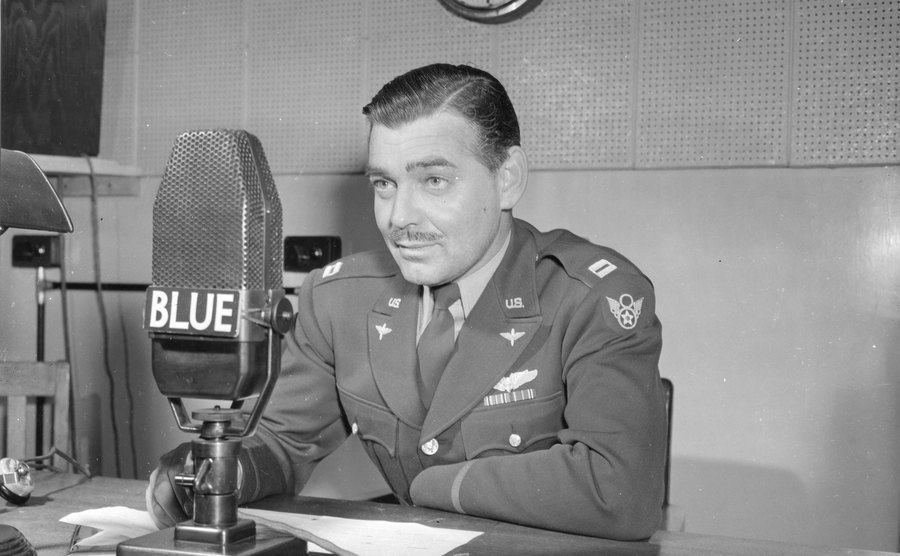 Capt. Clark Gable speaks into a microphone as he urges support for the war.