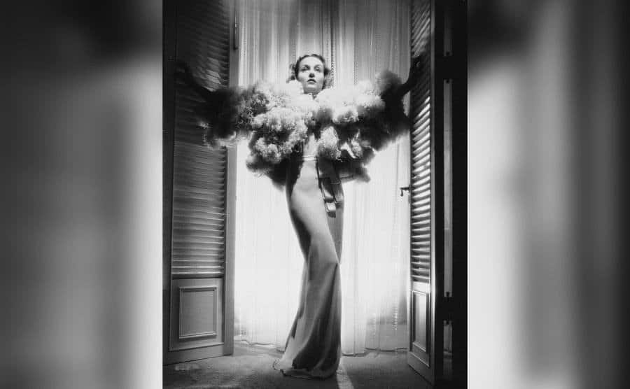 Carole Lombard stands framed by a doorway.