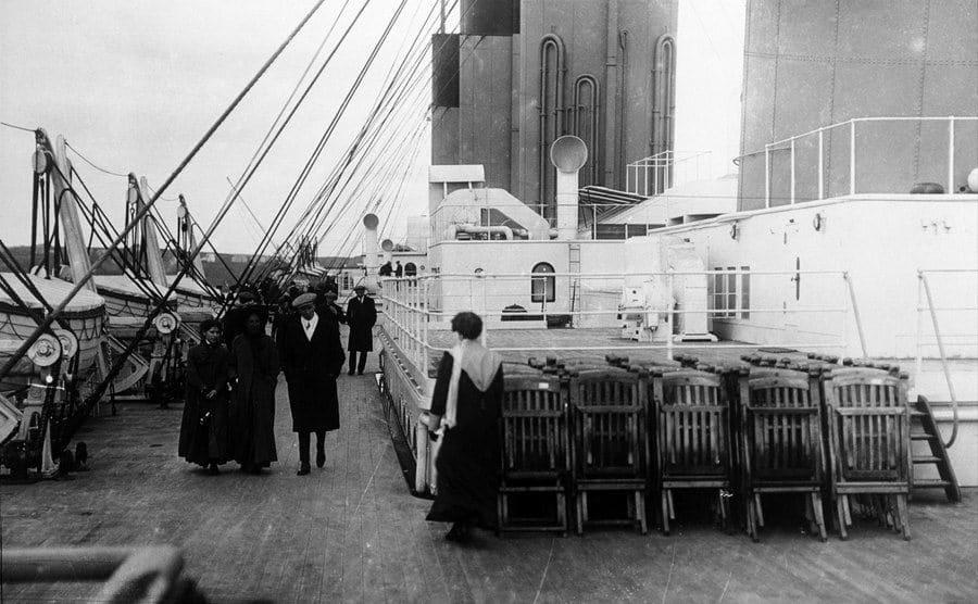 Passengers walk on the deck of the Titanic.