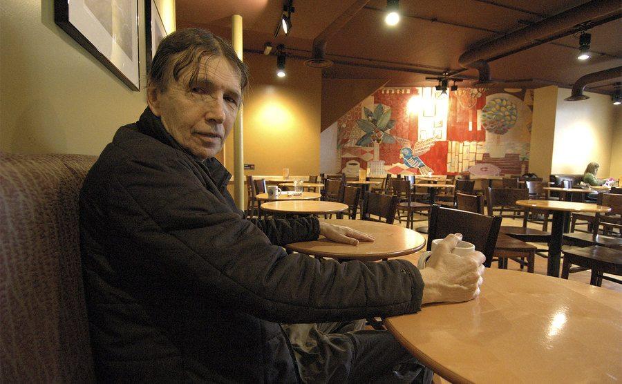 Charles Richard Webb is sitting in a coffee shop.