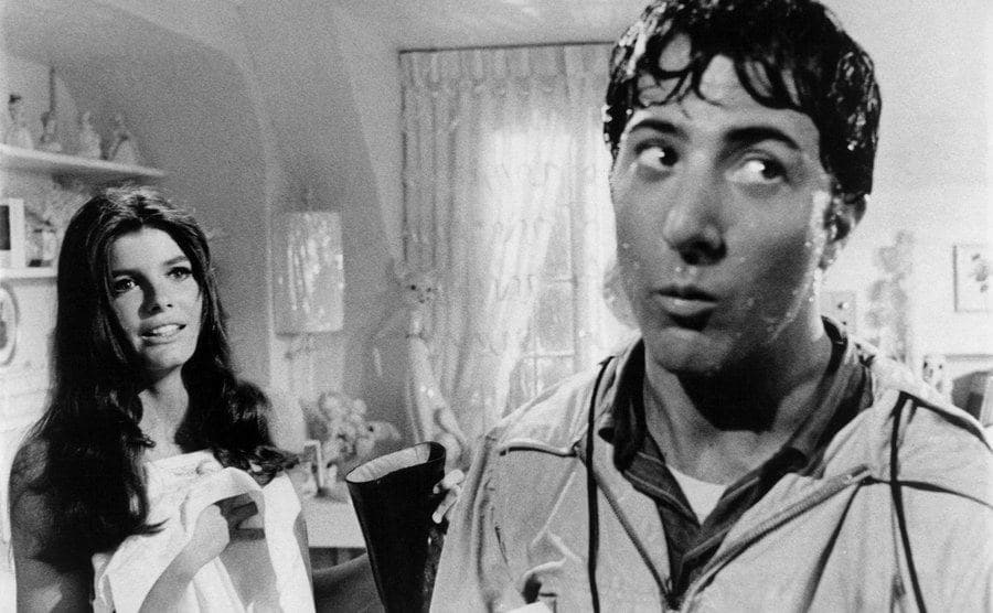 Katherine Ross covers herself with a sheet while Dustin Hoffman looks away awkwardly.