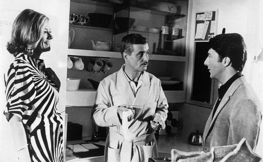 Elizabeth Wilson, William Daniels, and Dustin Hoffman are having a conversation in the kitchen in a scene from the film 'The Graduate.'