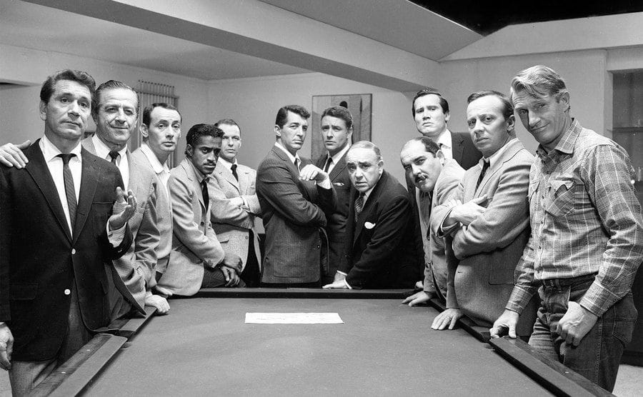 The cast of Ocean's 11 stands around a pool table.