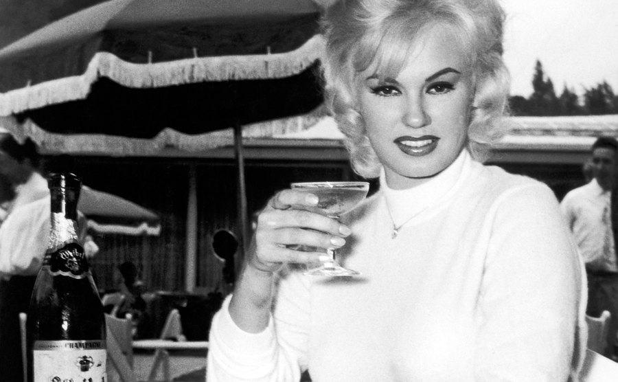 Mamie Van Doren enjoys a glass of champagne.