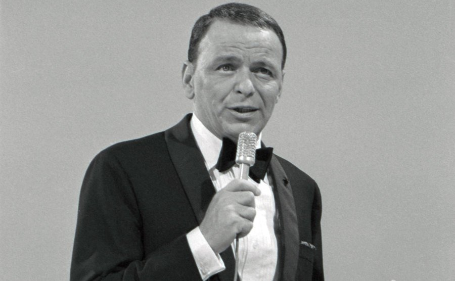 Frank Sinatra performs on stage.
