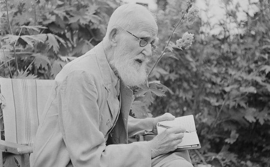 George Bernard Shaw is writing in the garden of his home.