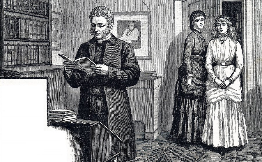 A man reads out of a book as two women stand by the door.