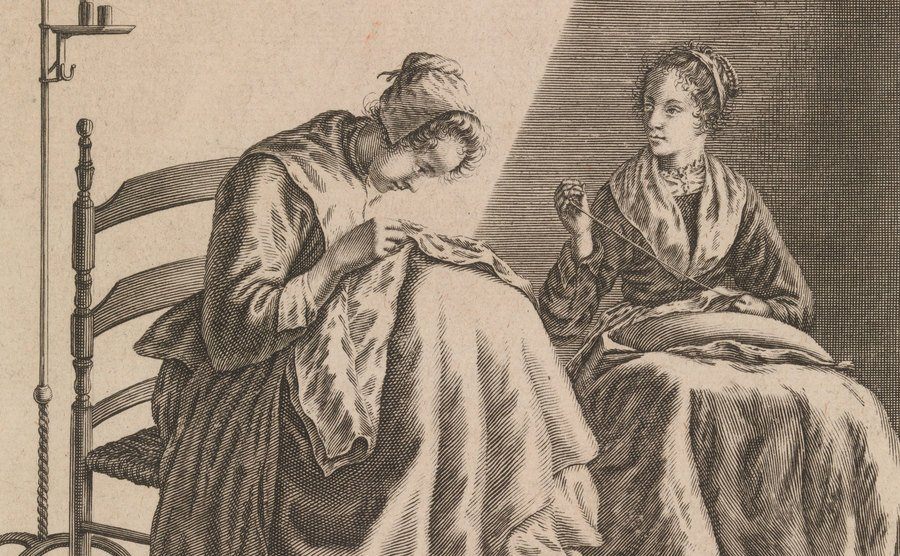 Two women sit, sewing dresses.