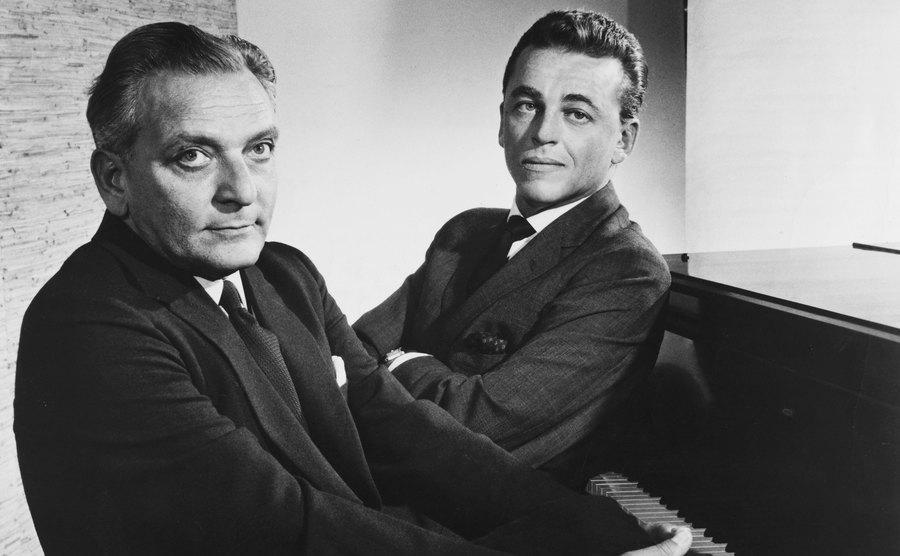 Frederick Loewe and Alan Jay Lerner sit at a piano.