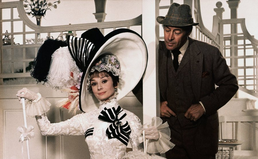 Audrey Hepburn sits in her iconic dress beside Rex Harrison in My Fair Lady.