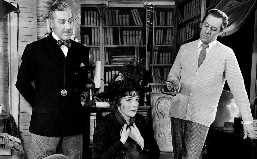 Rex Harrison and Reid Shelton look at Julie Andrews sitting on a sofa in My Fair Lady's play.