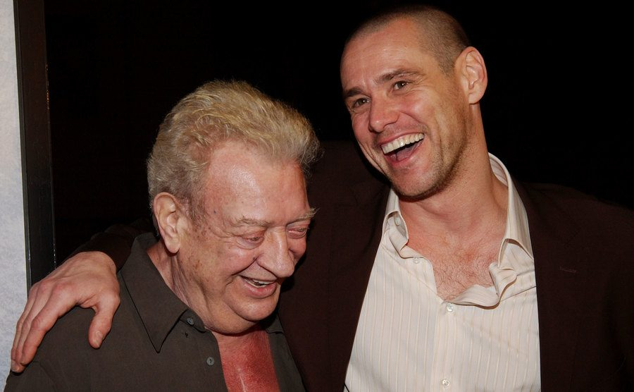 Rodney Dangerfield and Jim Carrey embrace and laugh.