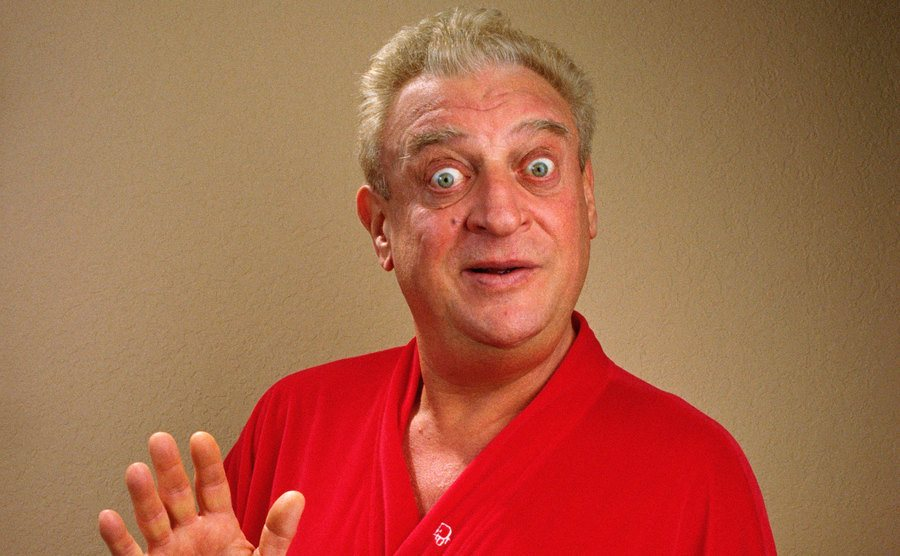 Rodney Dangerfield poses in a red robe.