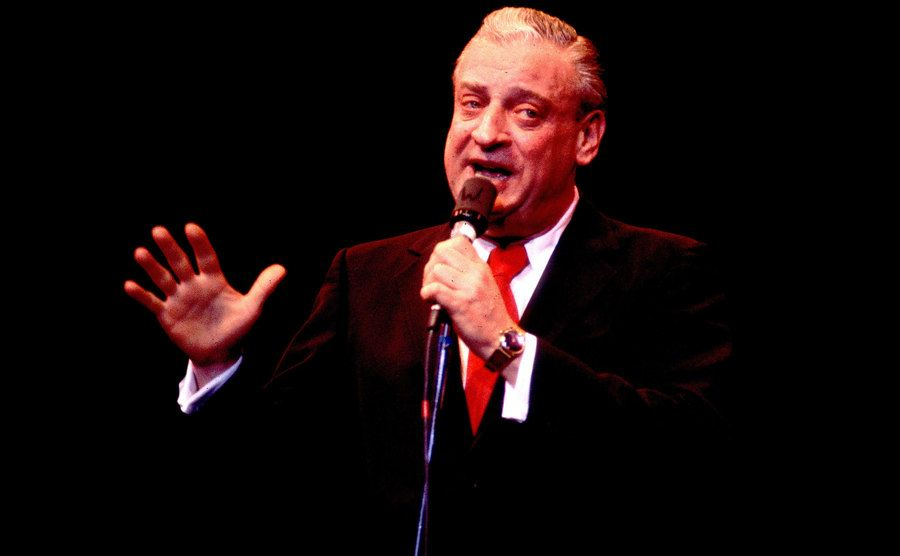 Rodney Dangerfield performs on stage.