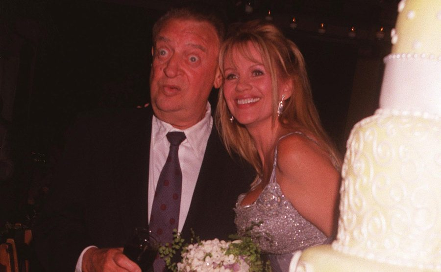 Joan and Rodney Dangerfield pose next to their wedding cake.
