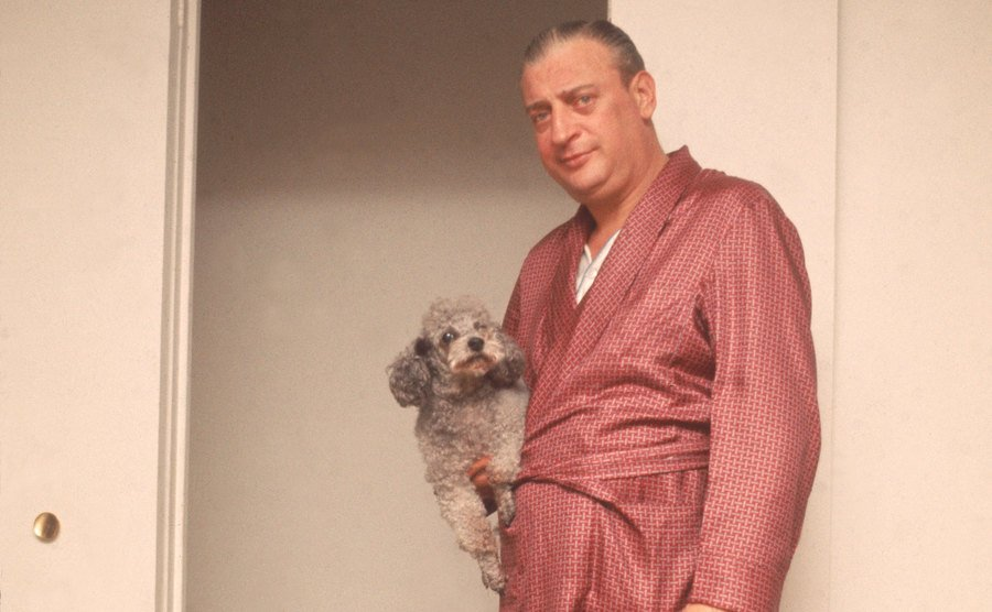 Rodney Dangerfield stands in a bathrobe as he holds his dog.