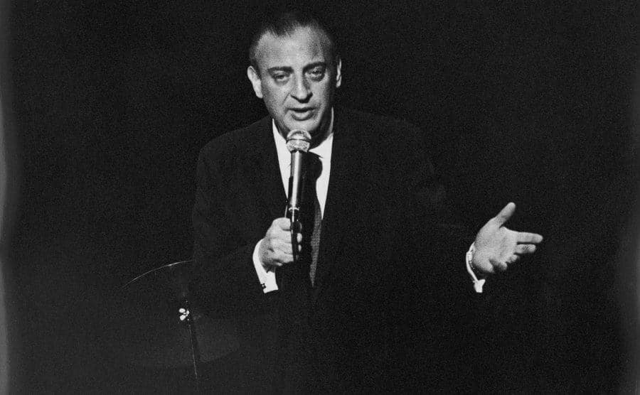 Rodney Dangerfield is performing on stage.