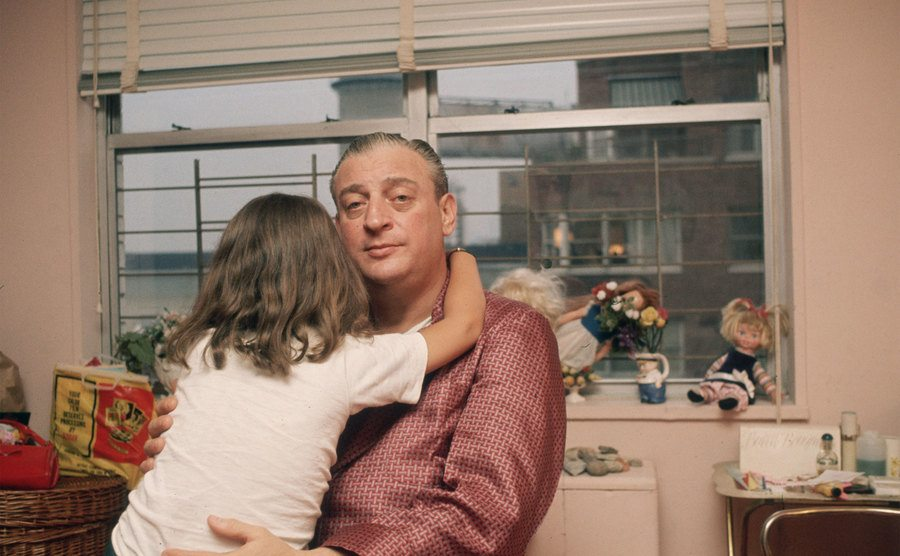 Rodney Dangerfield, dressed in silk pajamas, holds his daughter as she hugs his neck.