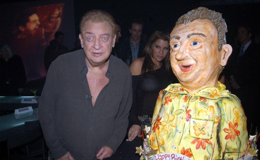 Rodney Dangerfield poses beside his 82nd birthday cake.