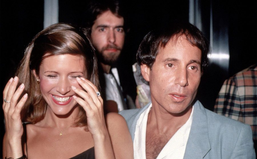 Carrie Fisher and Paul Simon during an event.