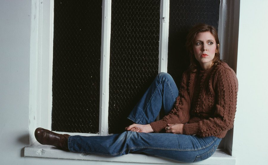 Carrie Fisher, in jeans and a brown sweater, sits on a window ledge.