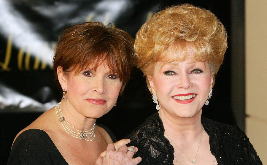 Carrie Fisher and her mother, Debbie Reynolds, attend an event.