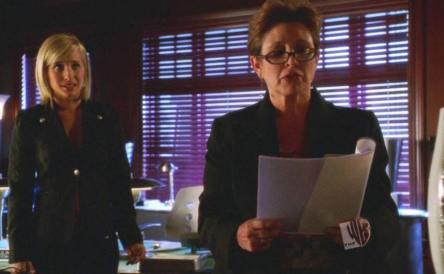 Carrie Fisher looks over a script in a scene from Smallville.