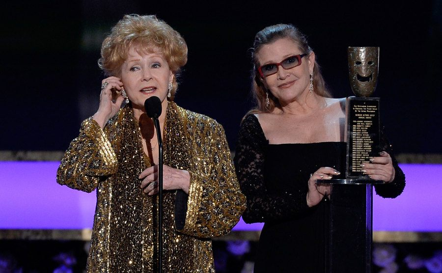 Debbie Reynolds and Carrie Fisher receive an award on stage.
