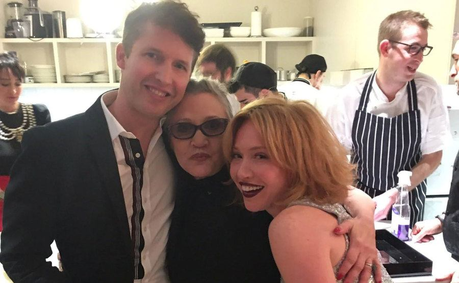 James Blunt, Carrie Fisher, and another woman embrace for a picture.