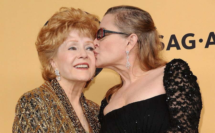 Carrie Fisher kisses Debbie Reynolds on the cheek.
