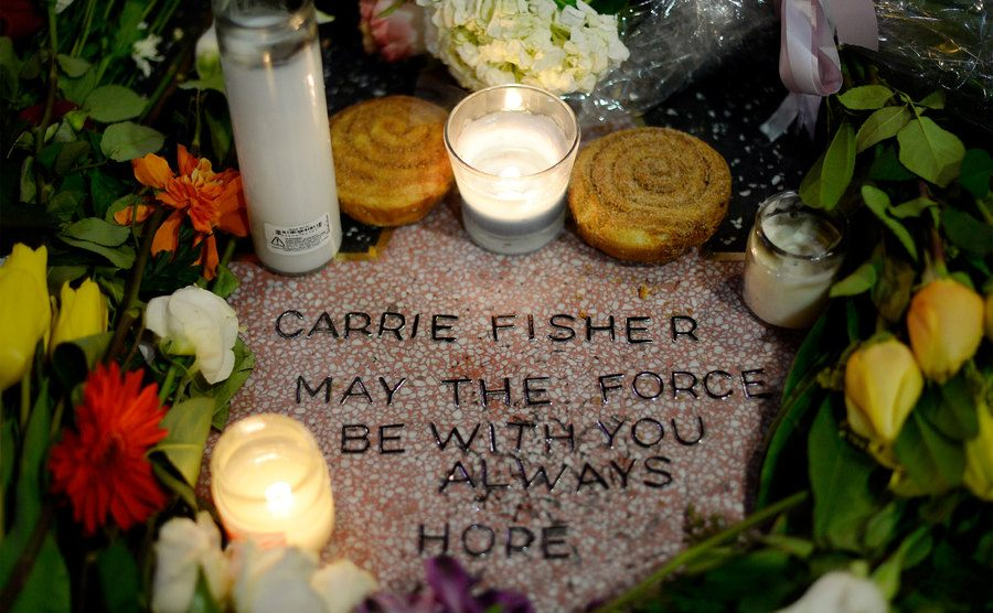 Candles and flowers are placed on actress Carrie Fisher's makeshift star.
